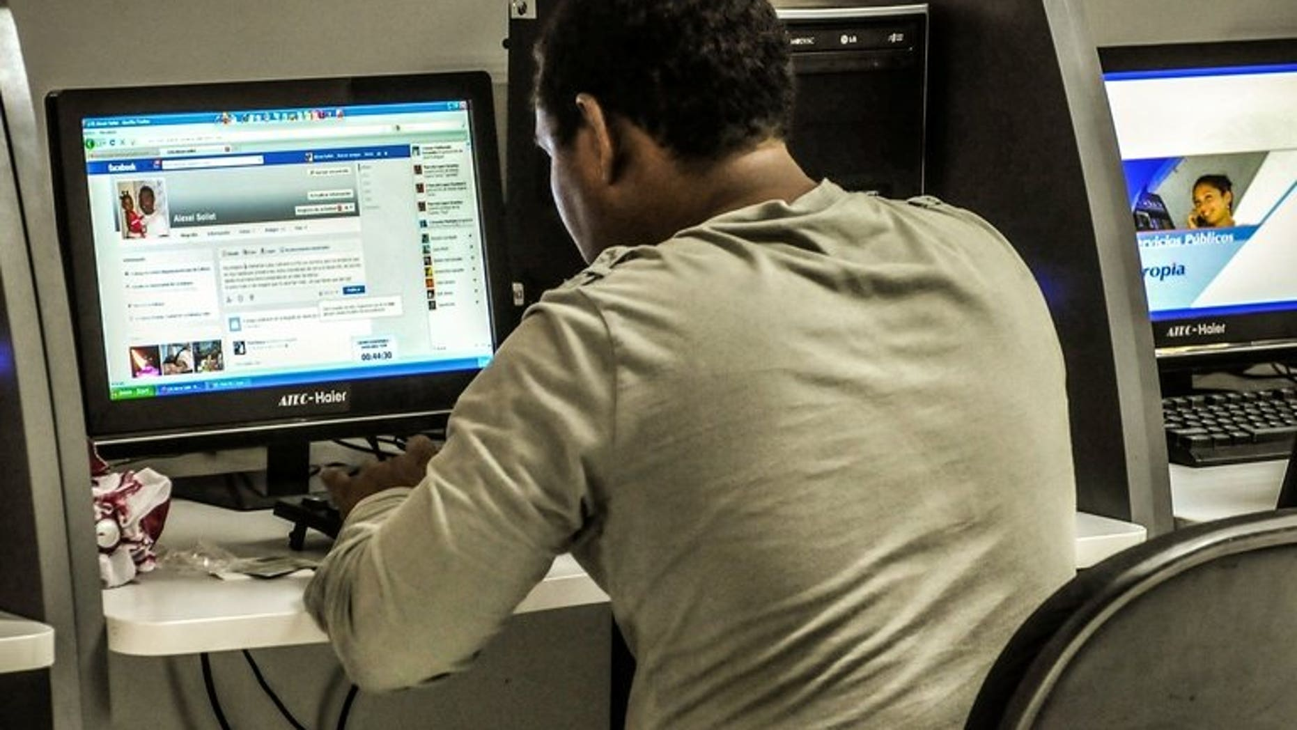 A man checks Facebook at a cyber cafe on June 4, 2013. Parents of a Canadian girl who killed herself after months of cyberbullying following a rape were sickened on Wednesday that her image was used to advertise an online dating service.