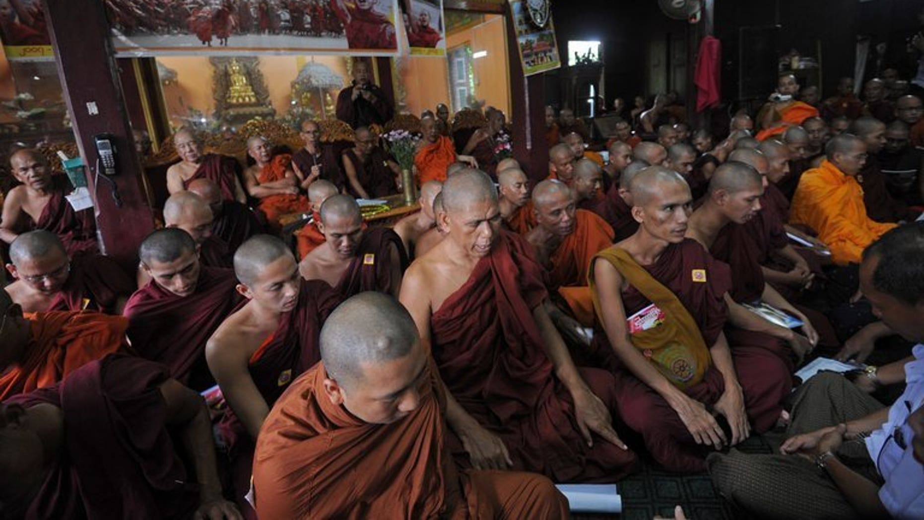 """Myanmar Buddhist monks pray during a gathering to mark the sixth anniversary of """"Saffron Revolution"""" at a monastery in Yangon on September 18, 2013."""