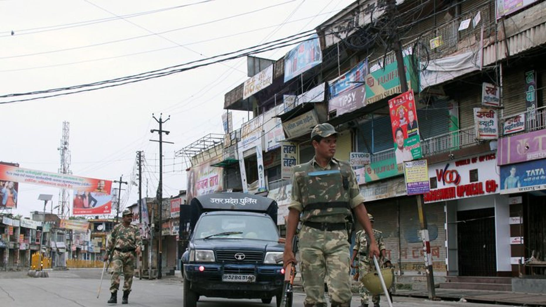 Indian soldiers patrol alongside a state police vehicle on a deserted street following communal riots between Muslims and Hindus in Muzaffarnagar, India's Uttar Pradesh state, on September 8, 2013.