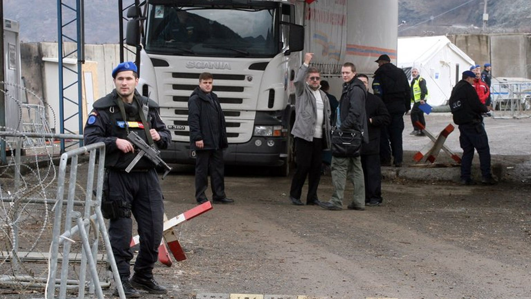 A Romanian officer of the European Union's police force in Kosovo stands guard in front of a truck carring Russian aid at the Jarinje border crossing between Serbia and northern Kosovo on December 13, 2011. Gunmen shot dead a member of the European Union's police force in Kosovo's flashpoint northern region Thursday, in the first deadly attack on the mission since its creation five years ago.