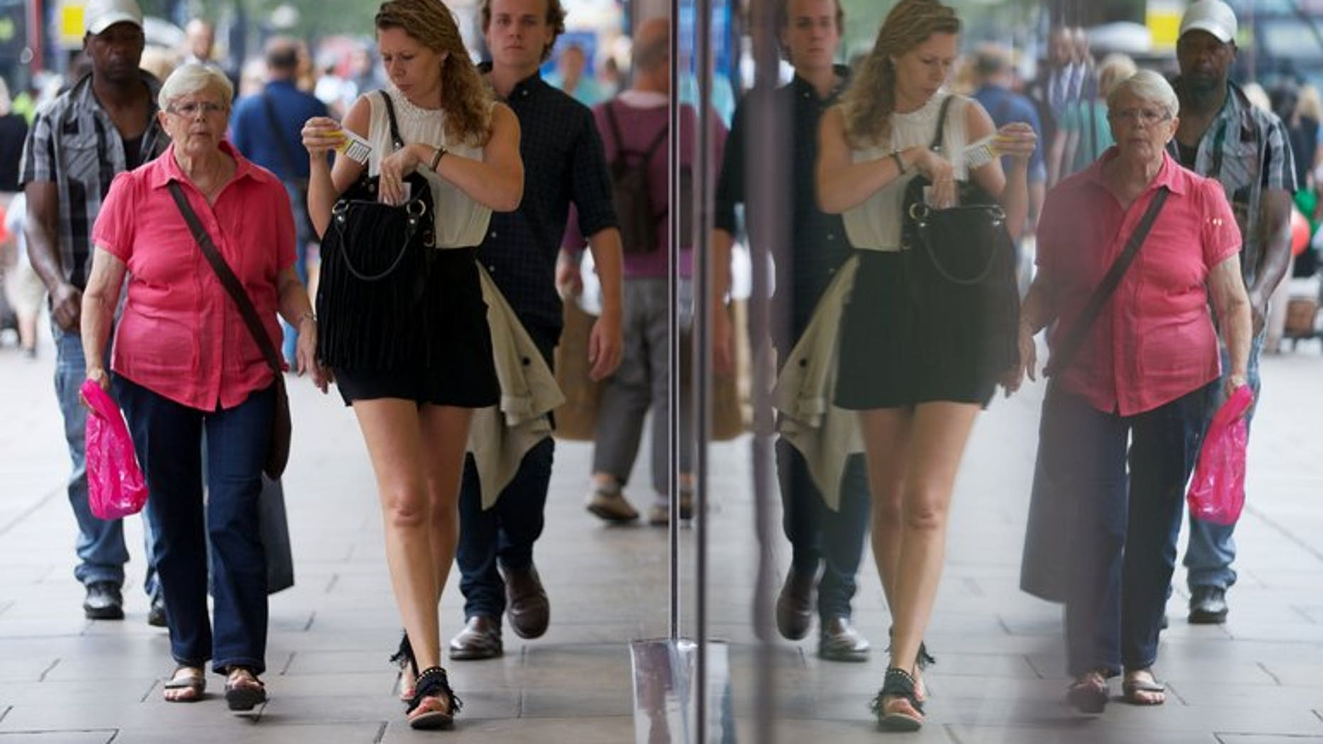 Shoppers are reflected in windows as they walk past a shop on Oxford Street in London on August 7, 2013. British retail sales fell unexpectedly in August after unusually hot weather in July had fuelled spending on food, drinks and summer clothing, official data has shown.