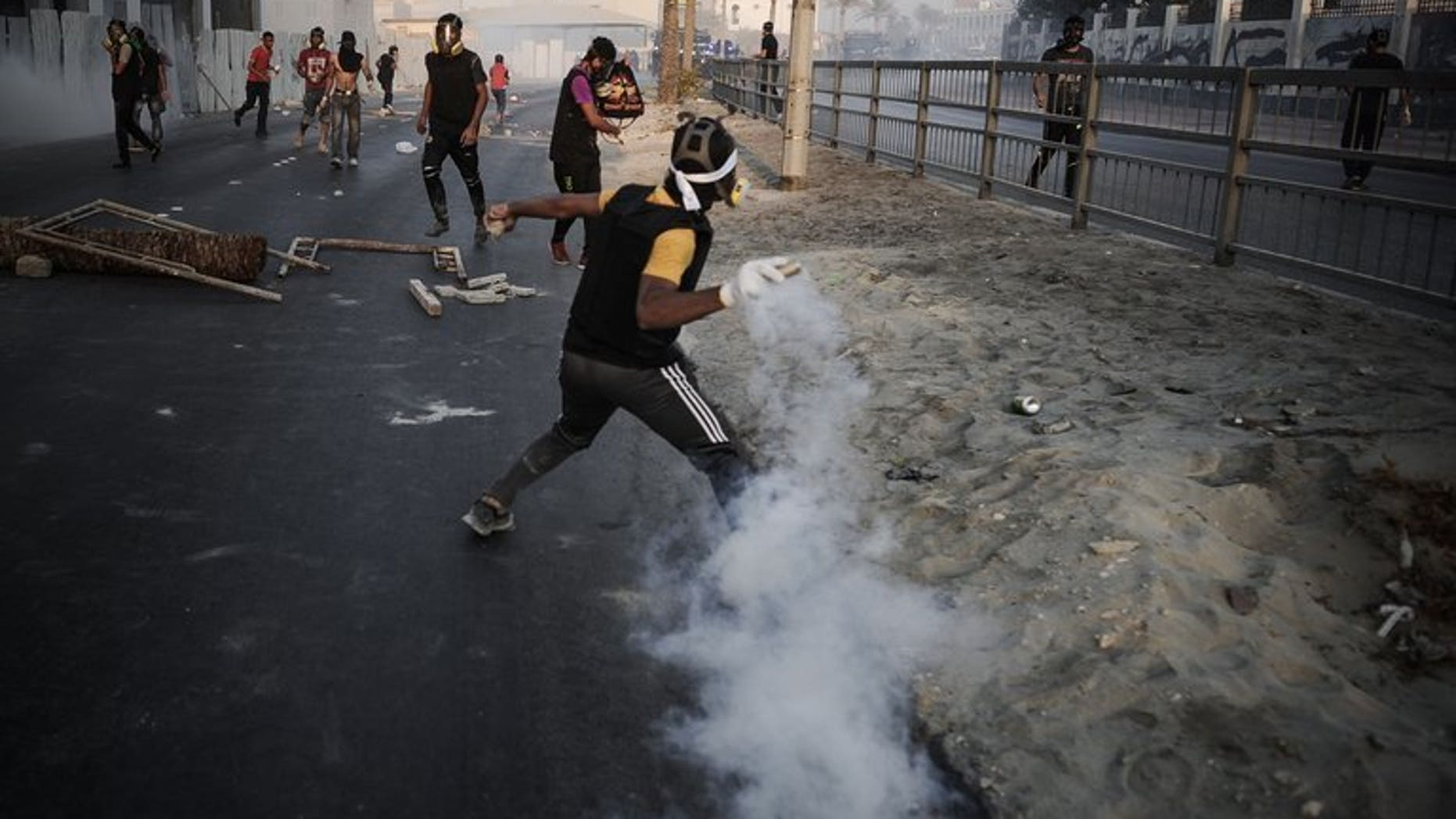 A Shiite protestor throws back a tear gas canister in the village of Daih, west of Manama, on Sunday. A Bahrain court on Thursday jailed five Shiites for periods up to 10 years after convicting them of attacking a government building with petrol bombs, a judicial source said.