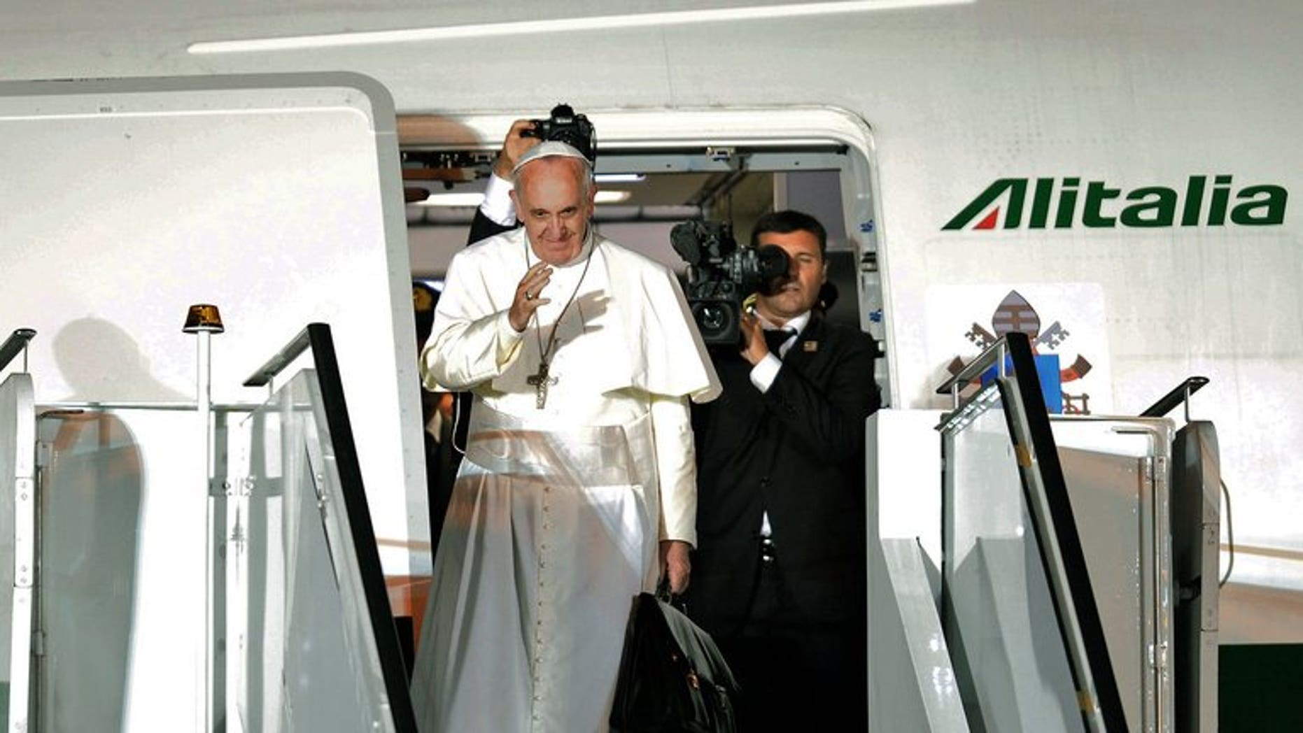 """Pope Francis waves as he boards the plane after a week-long trip to Brazil, on July 28, 2013. Pope Francis on Thursday lashed out at what he called the scandal of """"airport bishops"""", urging his peers to remain rooted in their dioceses and spend less time seeking the spotlight."""