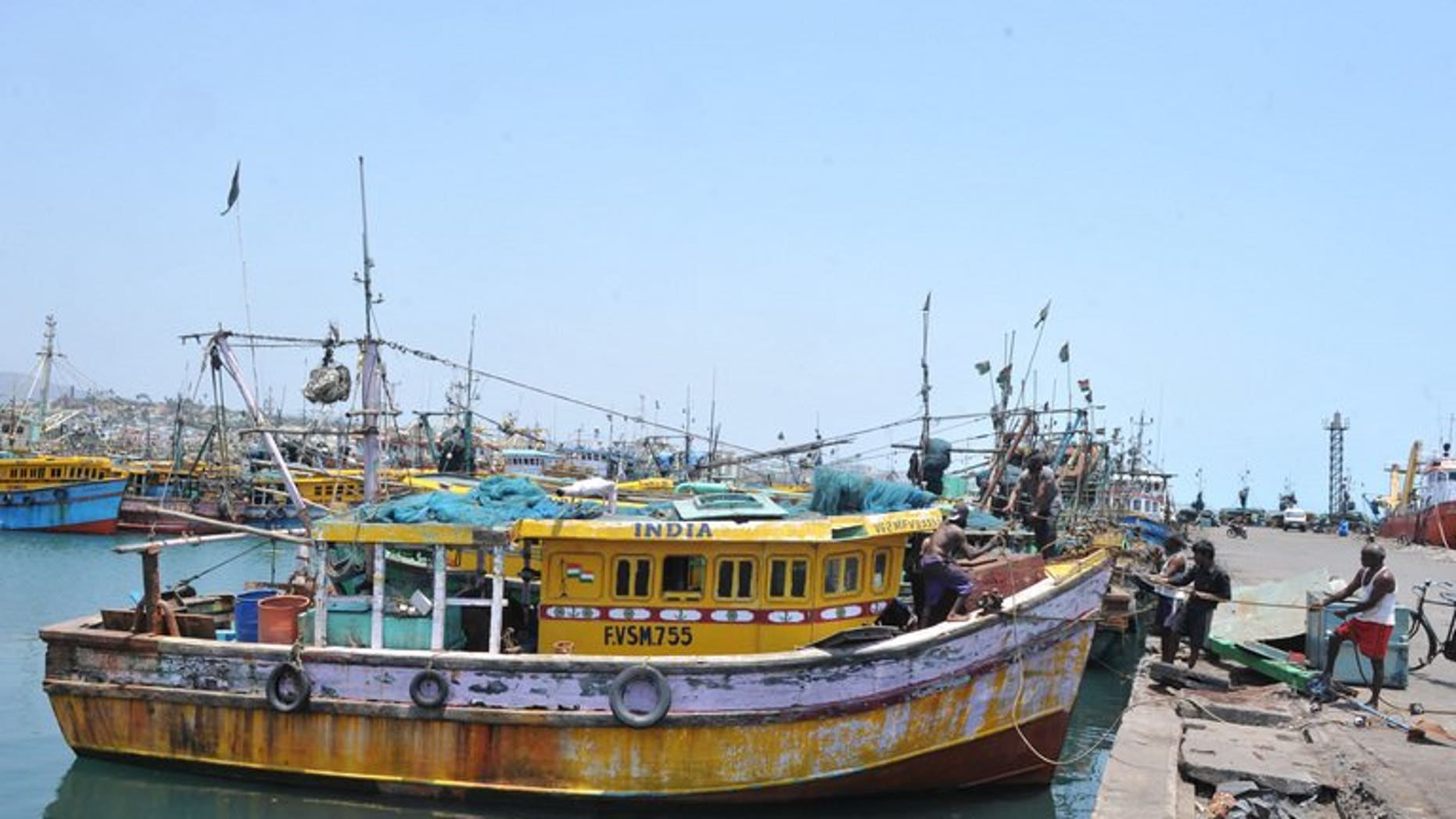 Indian fishermen work on the dockside in Visakhapatnam on April 9, 2012.