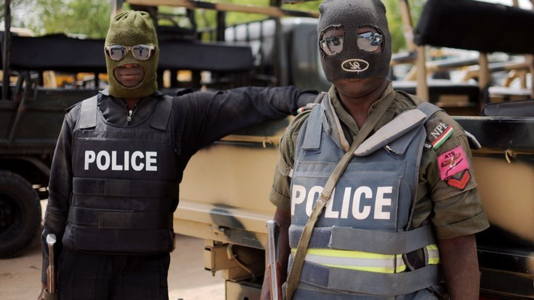 Nigerian police in Borno state pose prior to a patrol in former Boko Haram headquarters in Maiduguri on June 5, 2013.