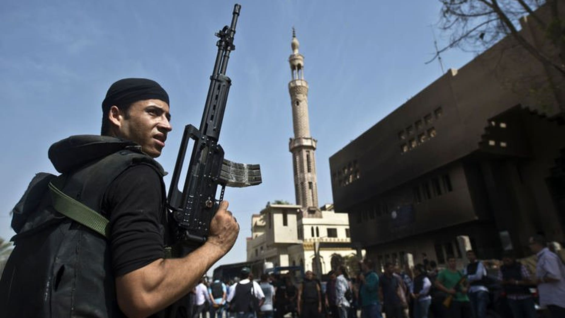 An Egyptian armed policeman holds in front of a burnt police station in the village of Kerdassah on the outskirts of Cairo, on September 19, 2013.