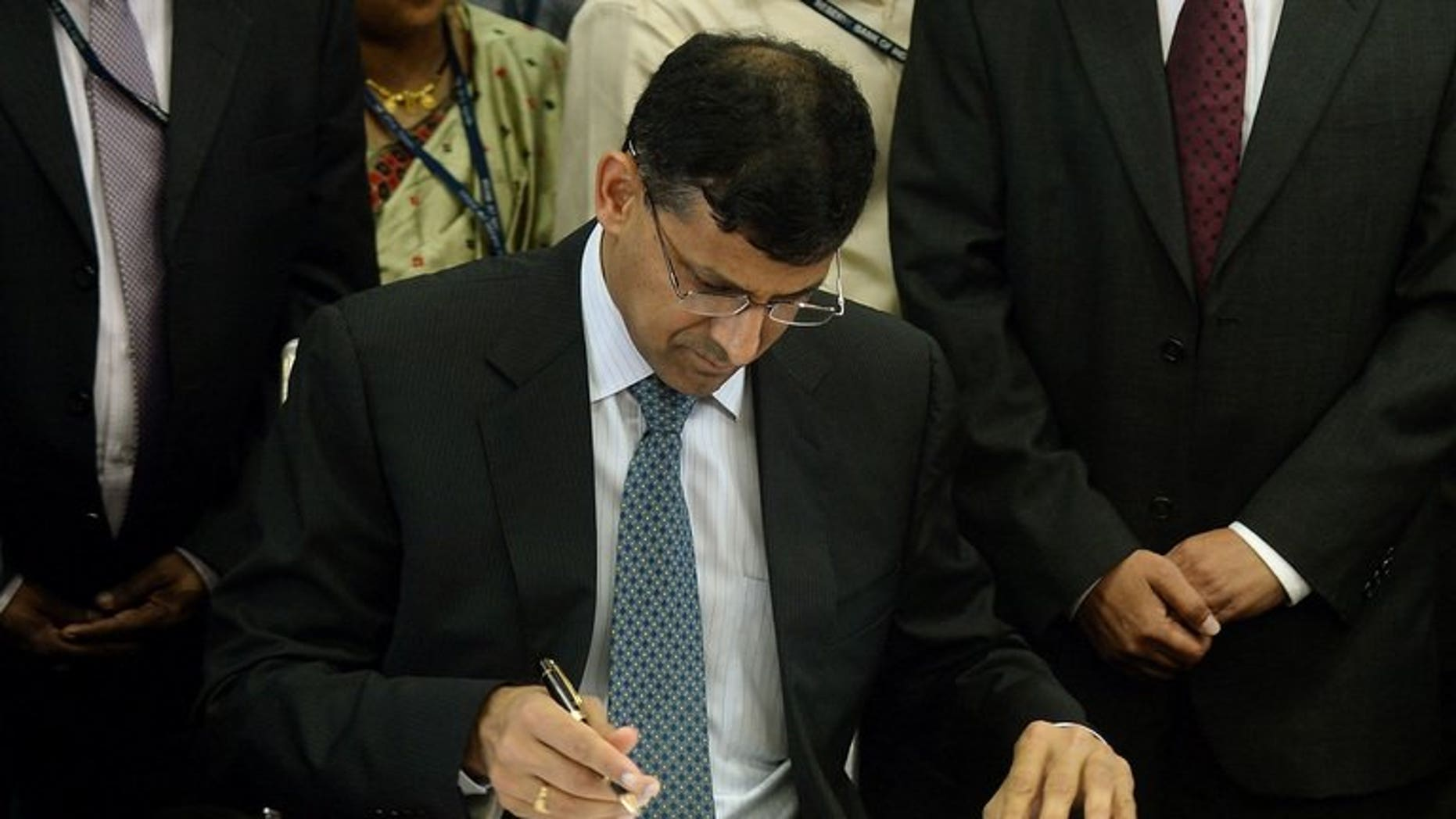 Reserve Bank of India's (RBI) newly appointed governor Raghuram Rajan signs official papers during the hand over ceremony at the RBI headquarters in Mumbai on September 4, 2013.