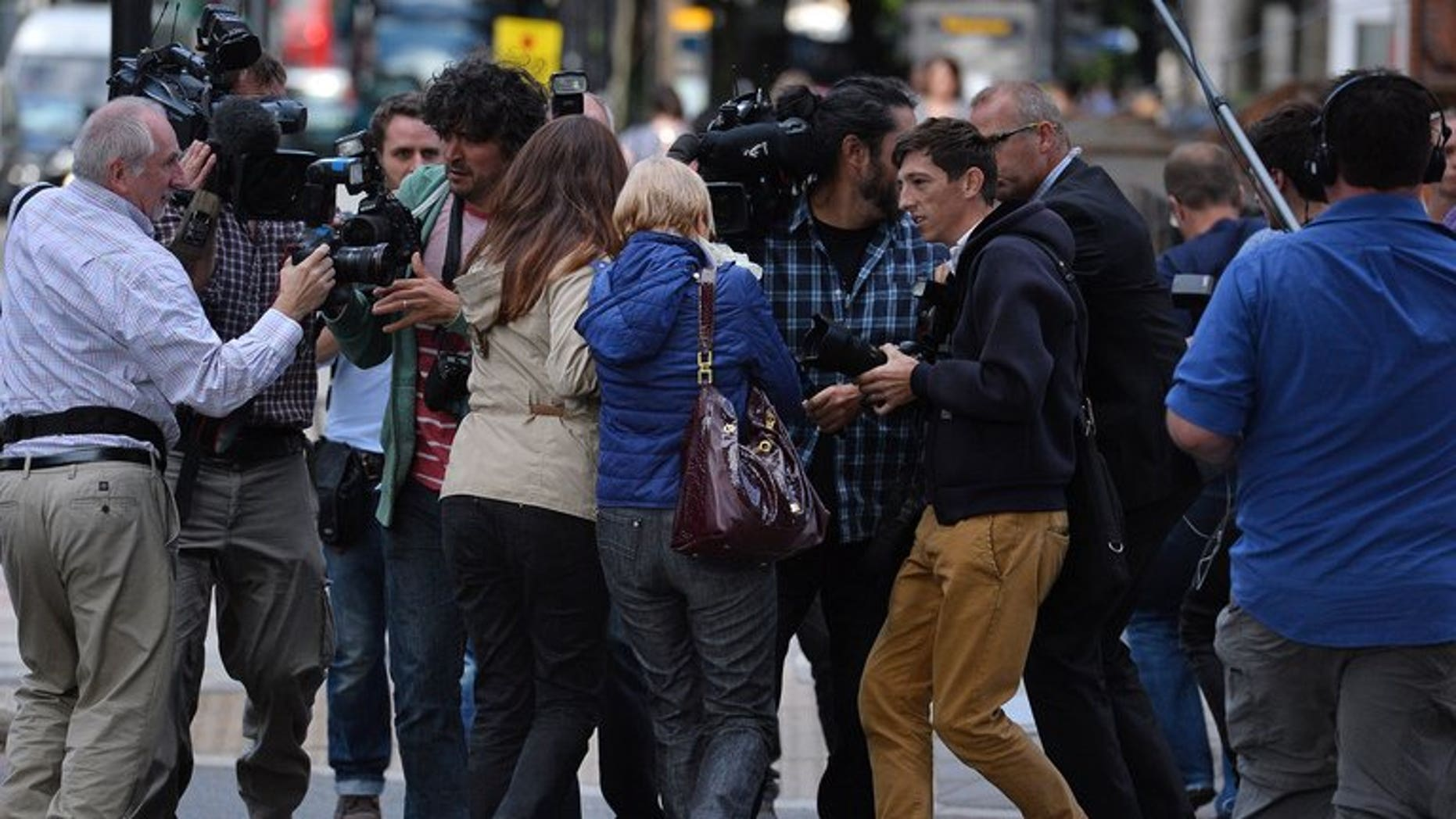 Anne (centre R) and Daniela Skinner (centre L), wife and daughter of alleged Mafia boss Domenico Rancadore, are pursued by the media, outside Westminster Magistrates court in London, on August 9, 2013.
