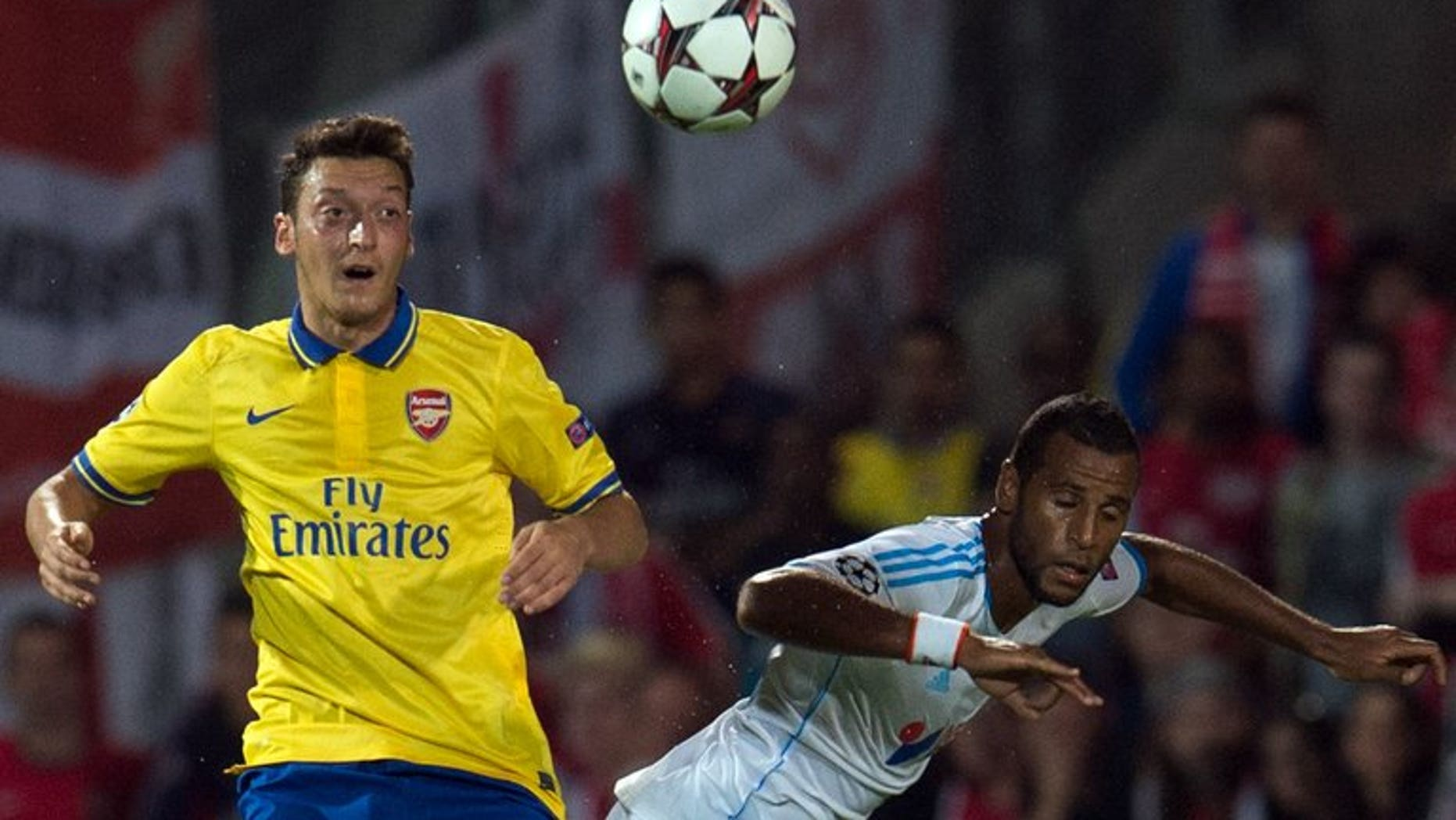 Mesut Ozil (left) clashes with Marseille's Jacques-Alaixys Romao at the Velodrome stadium on Wednesday. Arsenal manager Arsene Wenger has insisted club-record signing Mesut Ozil didn't leave Spanish giants Real Madrid because he wanted an easier life with the north London club.