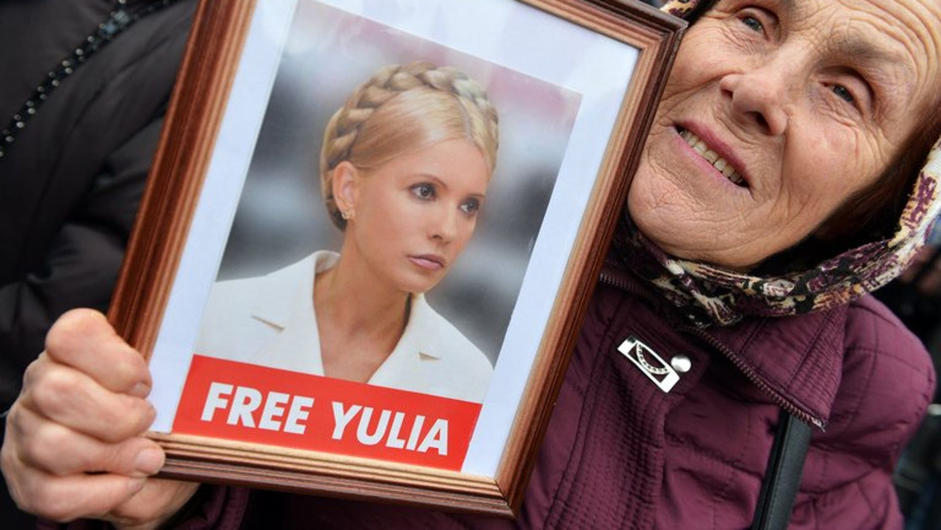 A protester holds a framed photo of jailled Ukrainian former prime minister Yulia Tymoshenko during an opposition rally in front of the central election commission in Kiev on November 6, 2012.