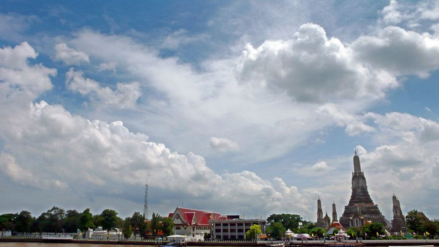 Thai motor boats sail on the Chao Phraya river along Wat Arun Buddhist temple in Bangkok, July 7, 2007.