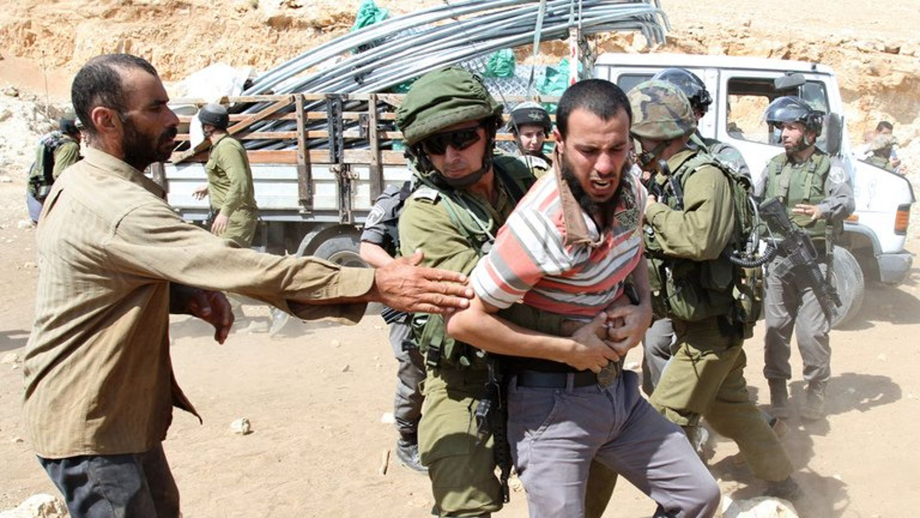 An Israeli soldier restrains a Palestinian man near a truck loaded with supplies on September 20, 2013 on a road leading to the West Bank village of Khirbet al-Makhul.