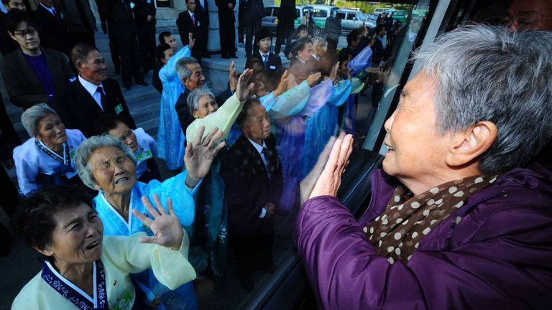Separated relatives wave goodbye after a family reunion in North Korea on November 5, 2010.