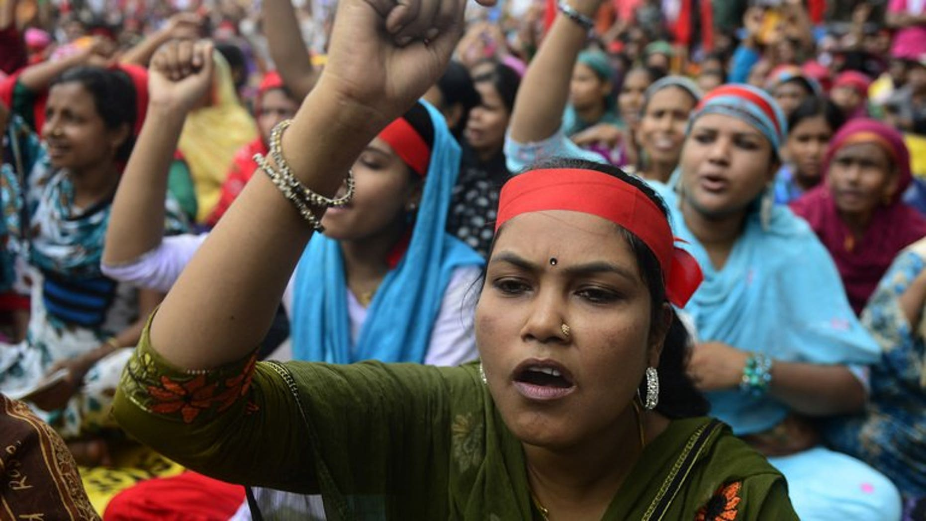 Bangladeshi garment workers shout slogans as they demand a wage increase during a rally in Dhaka, on September 13, 2013. Thousands of Bangladesh garment workers blocked roads and attacked factories outside the capital Dhaka, demanding a $100 minimum monthly wage.