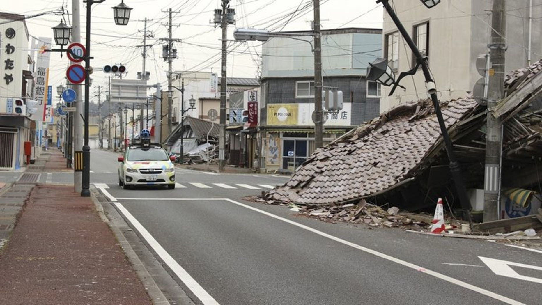 """A Google car mounted with a street view camera drives through a street in Namie, on March 28, 2013. namie -- a town abandoned after the Fukushima nuclear accident -- has protested Prime Minister Shinzo Abe's global promise that the situation of the crippled plant was """"under control""""."""