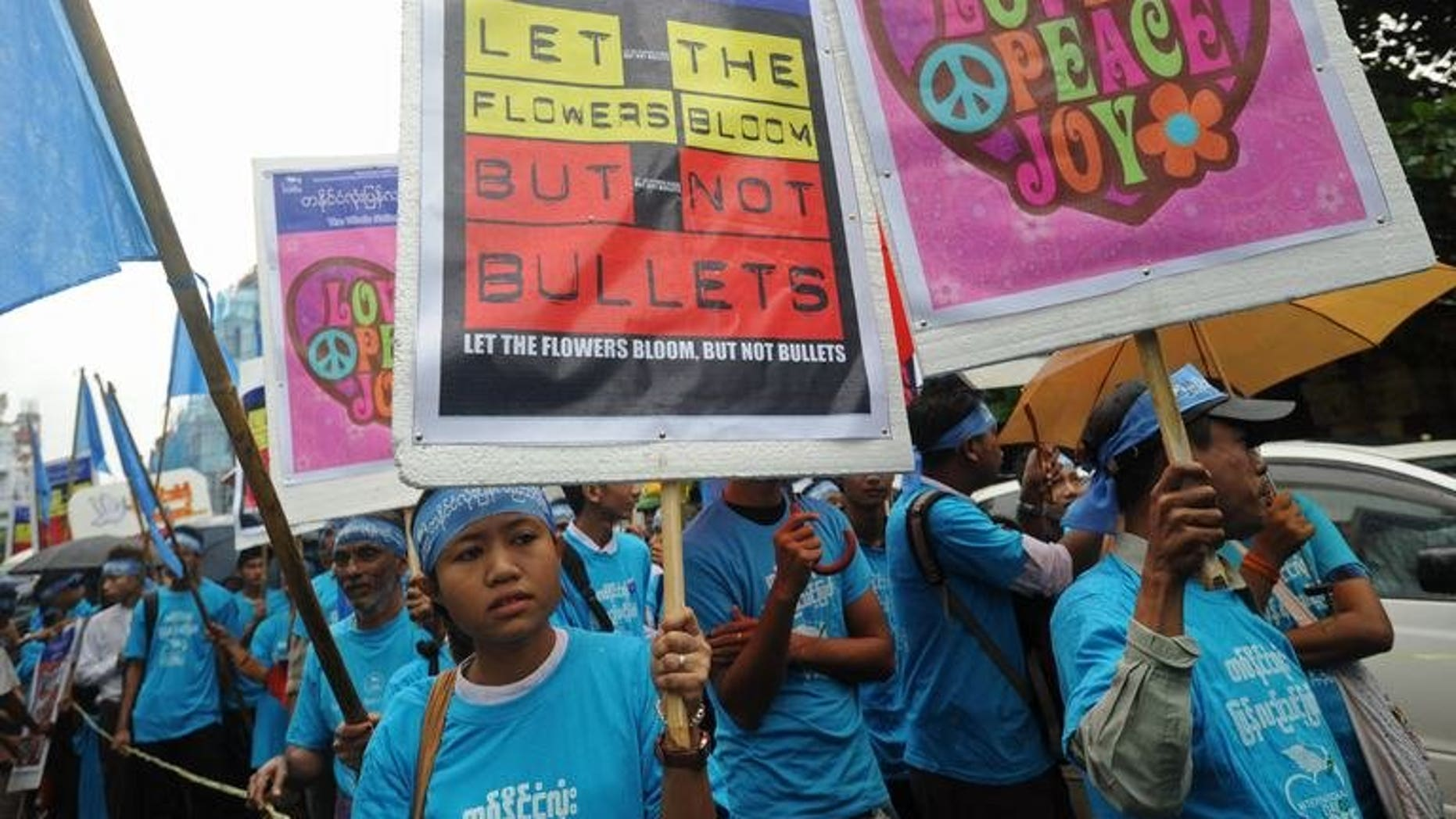 Myanmar activists hold placards as they march through Yangon, on September 21, 2013. Activists have praised Myanmar authorities for allowing a peace march through Yangon calling for an end to the nation's civil conflicts, after several people were charged for rallying without permission last year.