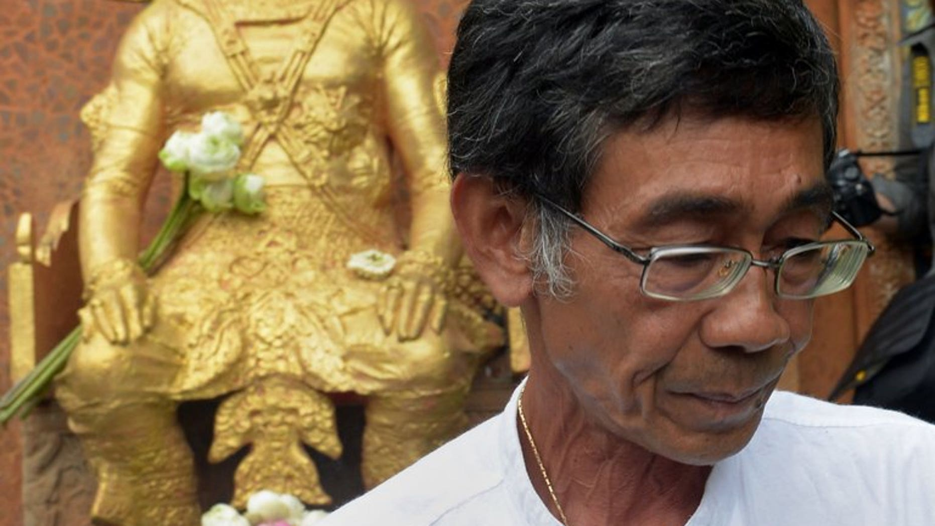 Cambodian Prince Sisowath Thomico walks past a statue of King Sisowath after praying and laying flowers during his hunger strike at Wat Phnom in Phnom Penh, on September 20, 2013. The prince has ended a hunger strike over disputed polls after military police expelled him from a pagoda where he was holding the protest fearing it would snowball.