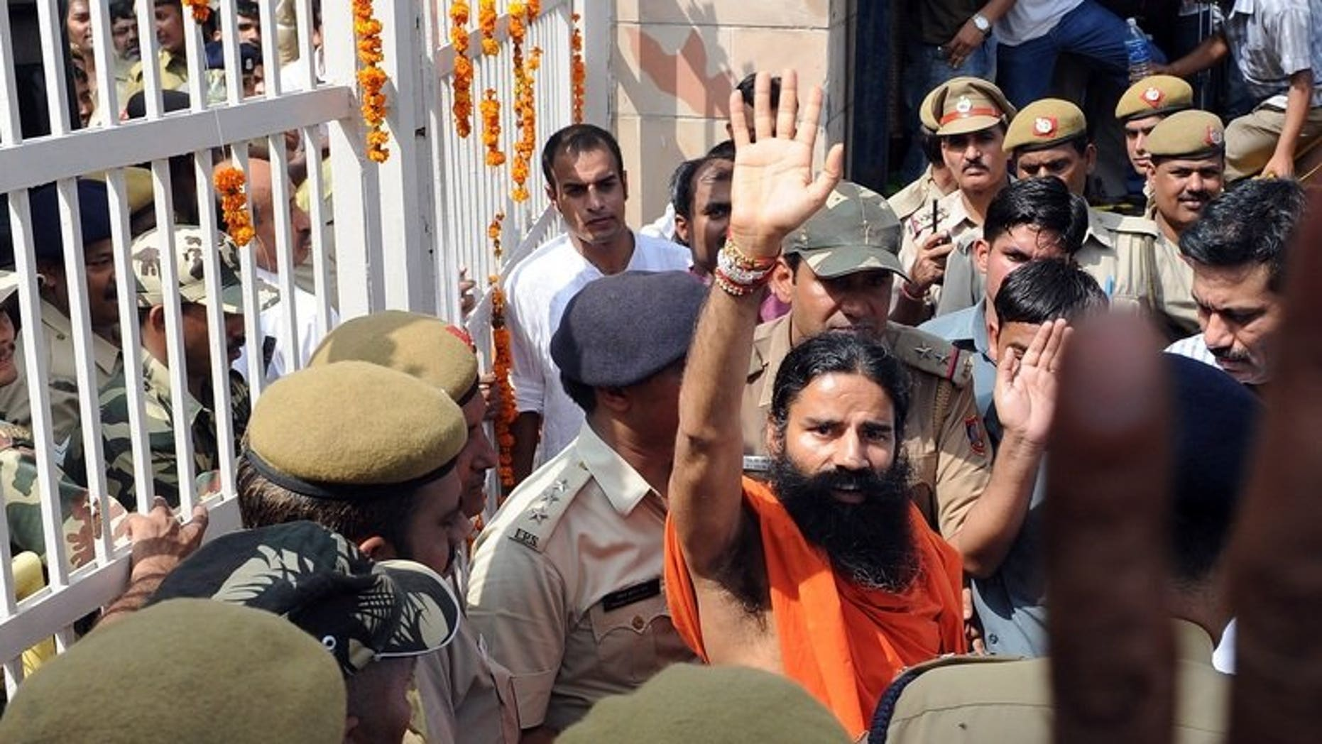 Yoga guru Swami Baba Ramdev (centre) waves to supporters of Indian social activist Anna Hazare as he comes out of Tihar prison during a protest in New Delhi on August 17, 2011. Swami Ramdev, who heads a global yoga empire, was detained Saturday at London's Heathrow airport and questioned for six hours by British customs officials, the Press Trust of India reported.