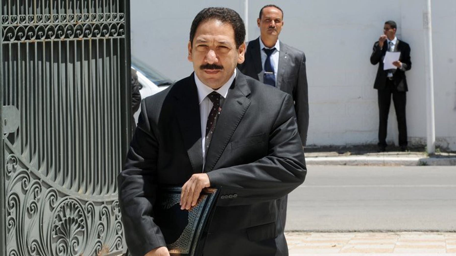 Tunisian Interior Minister Lotfi Ben Jeddou (C) arrives at the Prime Minister's office in Cathage on August 3, 2013.