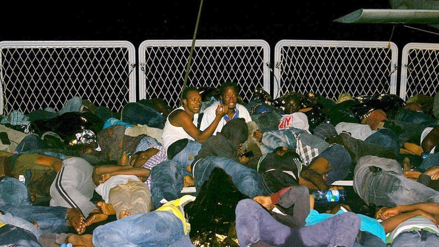 Mainly Syrian refugees rest aboard a boat after being rescued overnight by the Italian Navy near the Italian port of Pozzallo, south of Sicily on September 16, 2013.