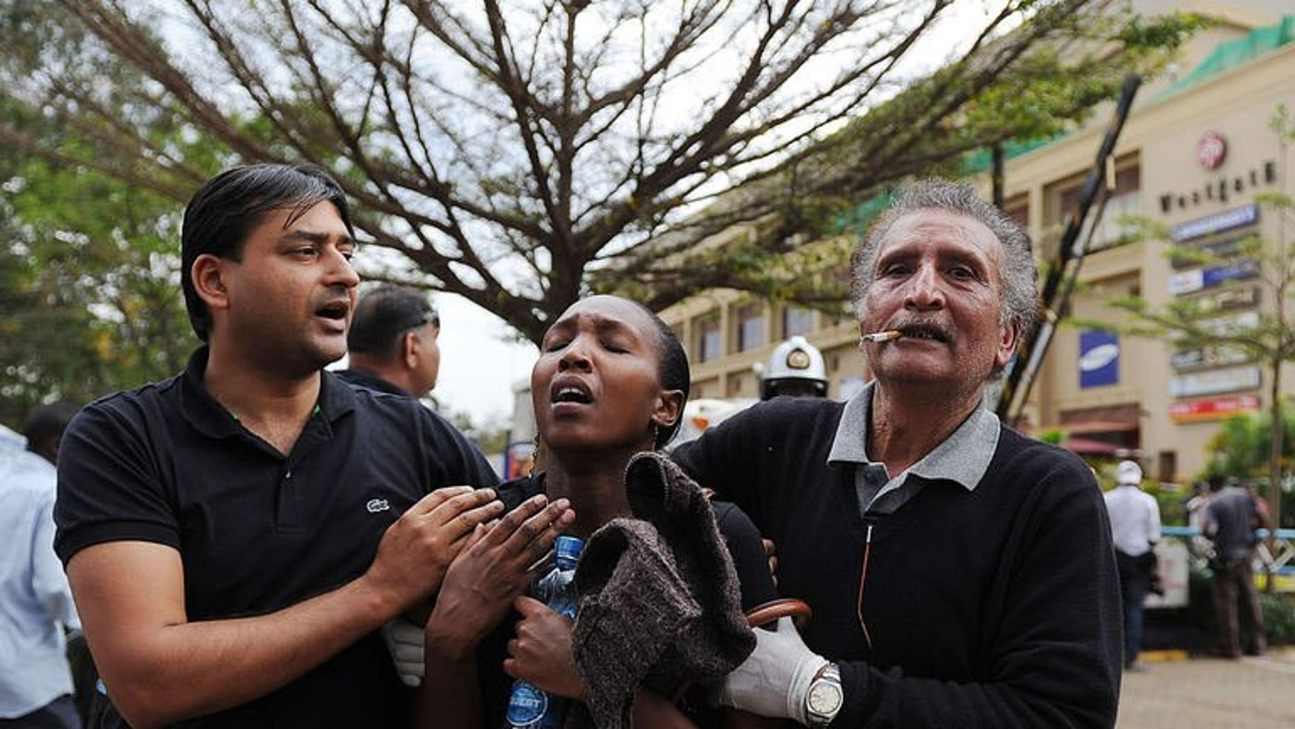A woman (C) who had been held hostage reacts in shock on September 21, 2013 after she was freed following a security operation at an upmarket shopping mall in Nairobi where suspected terrorrists engaged Kenyan security forces in a drawn out gun fight.