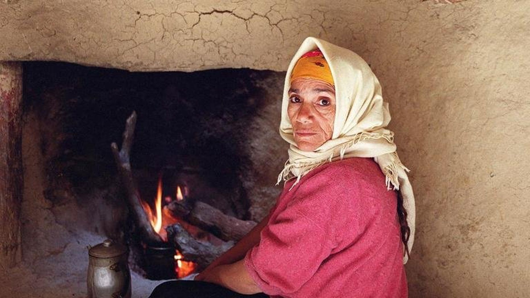A woman who has never known gas or electricity warms herself 19 February 2001 by a fire in a makeshift home in Cherrata, 100 kms south of Algiers. General Electric Co. has won a $2.2 billion contract to provide turbines for six power plants in Algeria, state energy giant Sonatrach announced on Sunday.