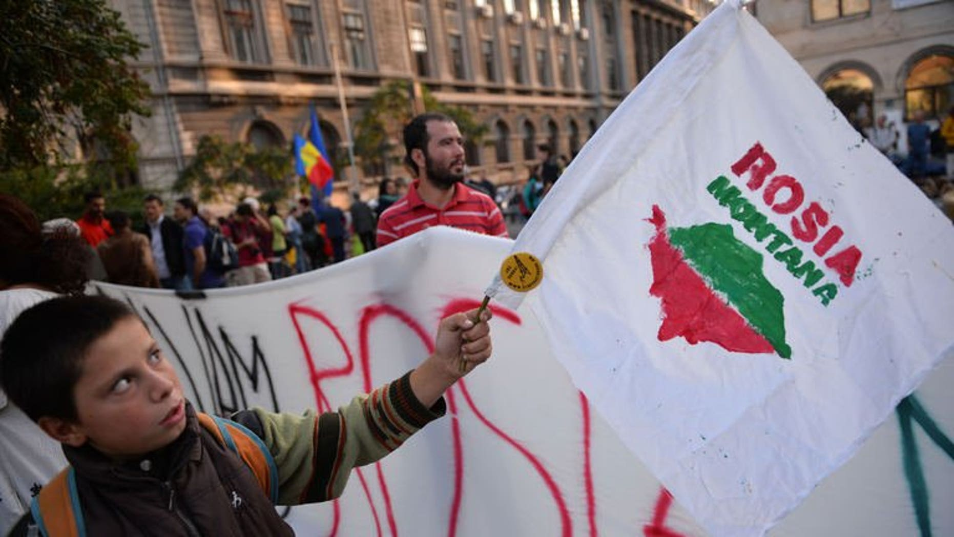 "A child waves a flag with the logo of ""Save Rosia Montana"" NGO during the 22nd day of demonstrations in Bucharest against the Rosia Montana Gold Corporation (RMGC), a Canadian gold mine project using cyanide, on September 22, 2013."