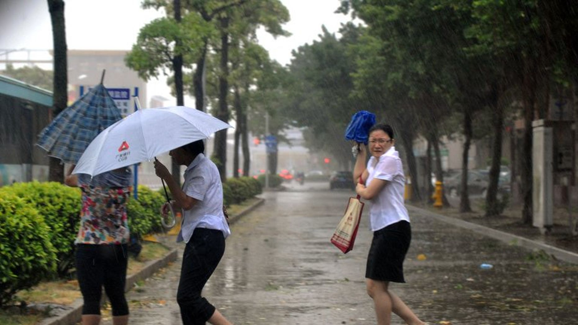 People take cover in Shantou, southern China, on September 22, 2013. Typhoon Usagi has left 25 people dead in southern China's Guangdong province, state media reported.