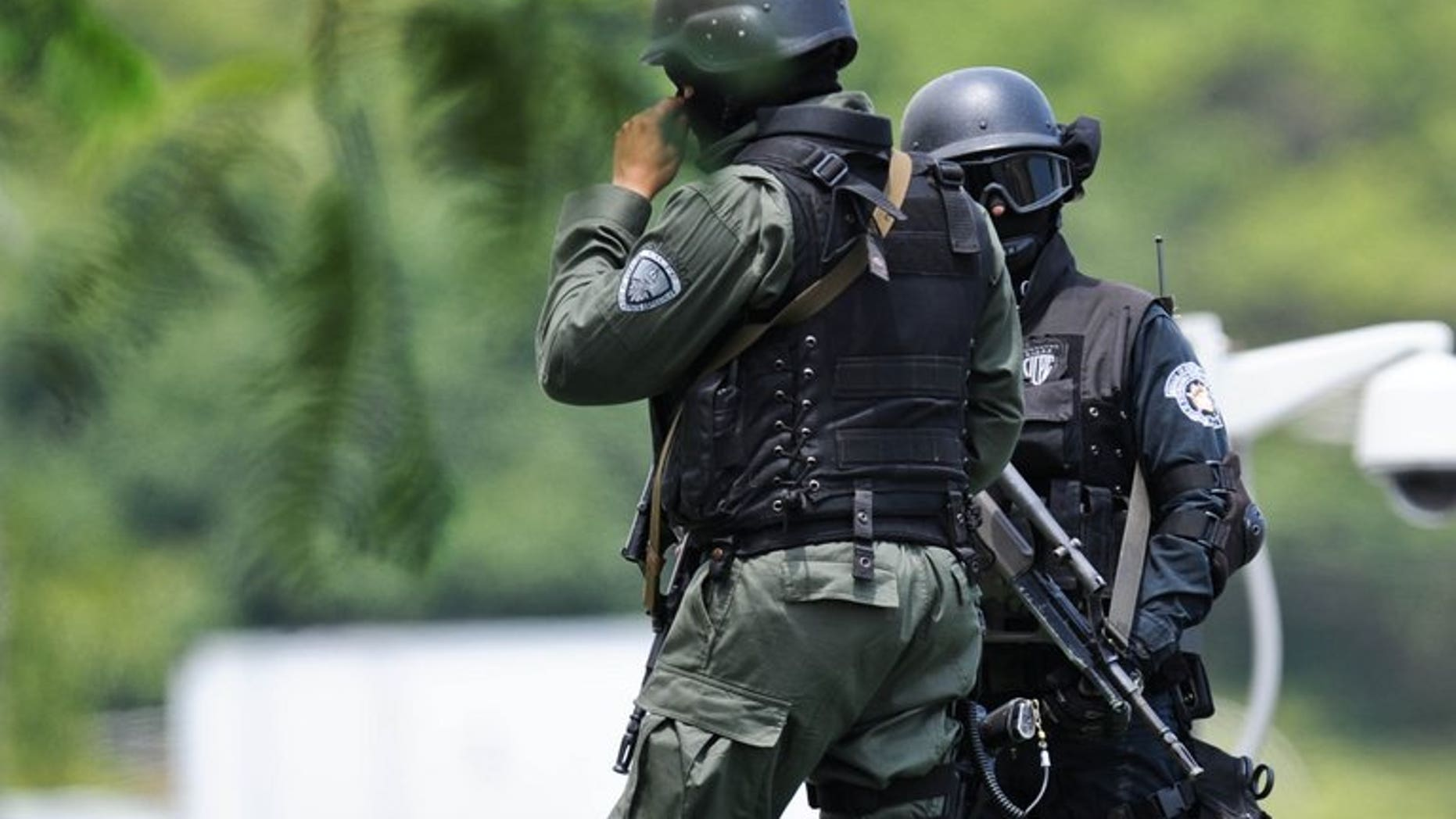 Police stand guard at the airport in Caracas. Three members of Venezuela's security forces have been arrested in connection with the 1.3 tonnes of cocaine French police found aboard an Air France flight that originated in Caracas.
