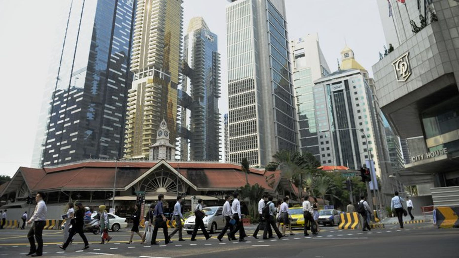 Workers head to work at Singapore's central business district on August 23, 2011. Singapore announced tighter rules on the hiring of foreign professional workers, saying companies will from next year have to show proof they first tried to recruit local citizens