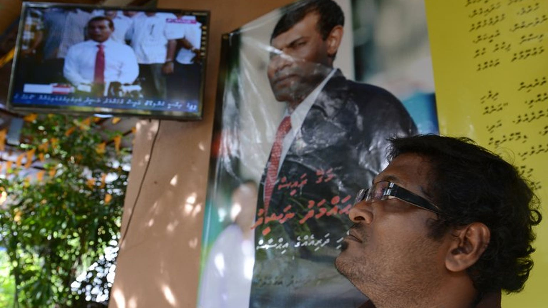A Maldivian national watches a televised live press conference in Sri Lanka's capital Colombo on September 8, 2013.