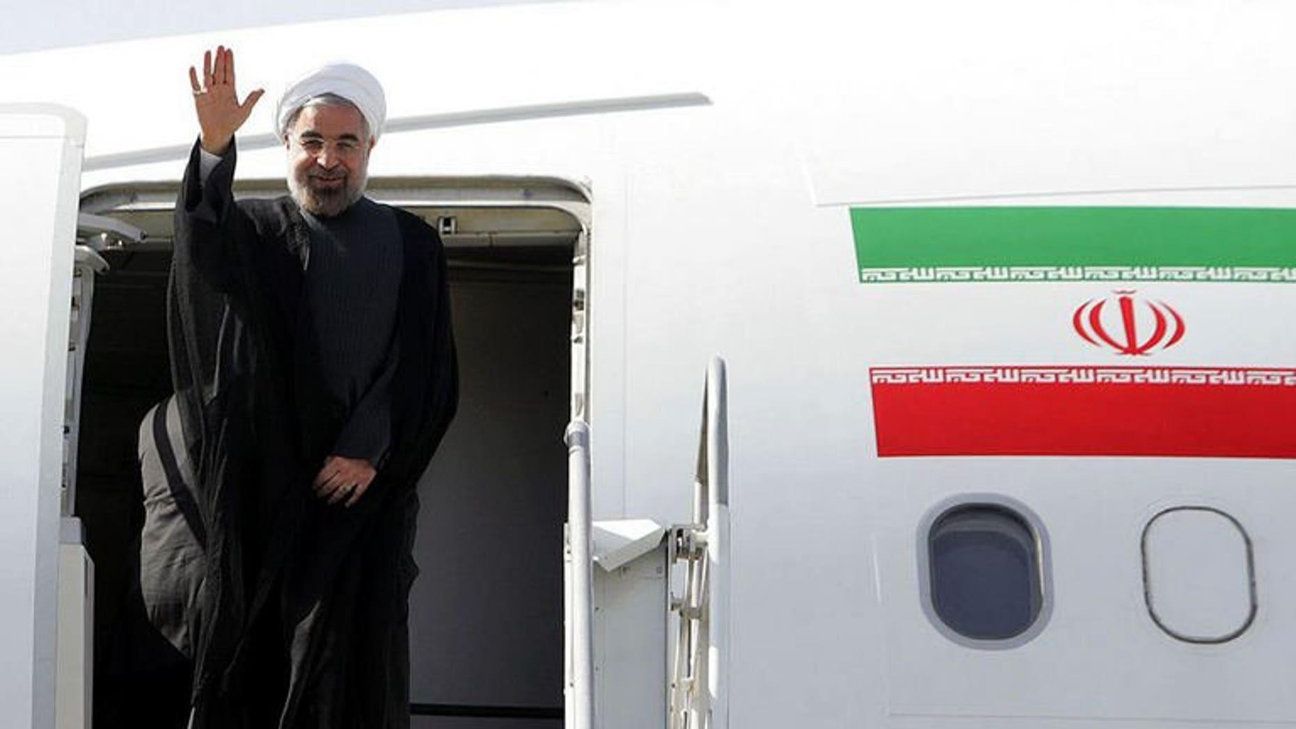 A handout picture released by the Iranian presidency shows President Hassan Rowhani waving before entering an airplane to attend the UN General Assembly, at Tehran's Mehrabad Airport on September 23, 2013.