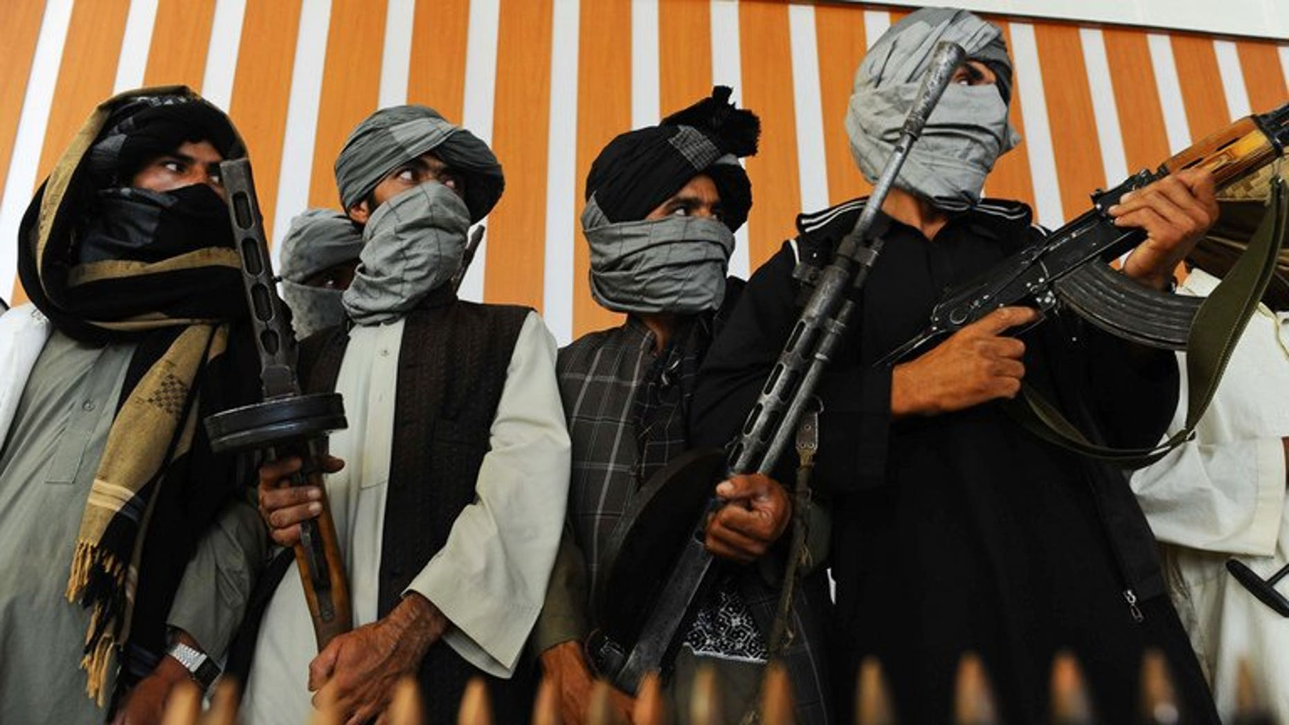 Taliban fighters stand with their weapons during a ceremony in Herat, western Afghanistan, on August 7, 2013. Mortar shells fired from Afghanistan have hit a border village in northwest Pakistan, killing two civilians, security officials told AFP.