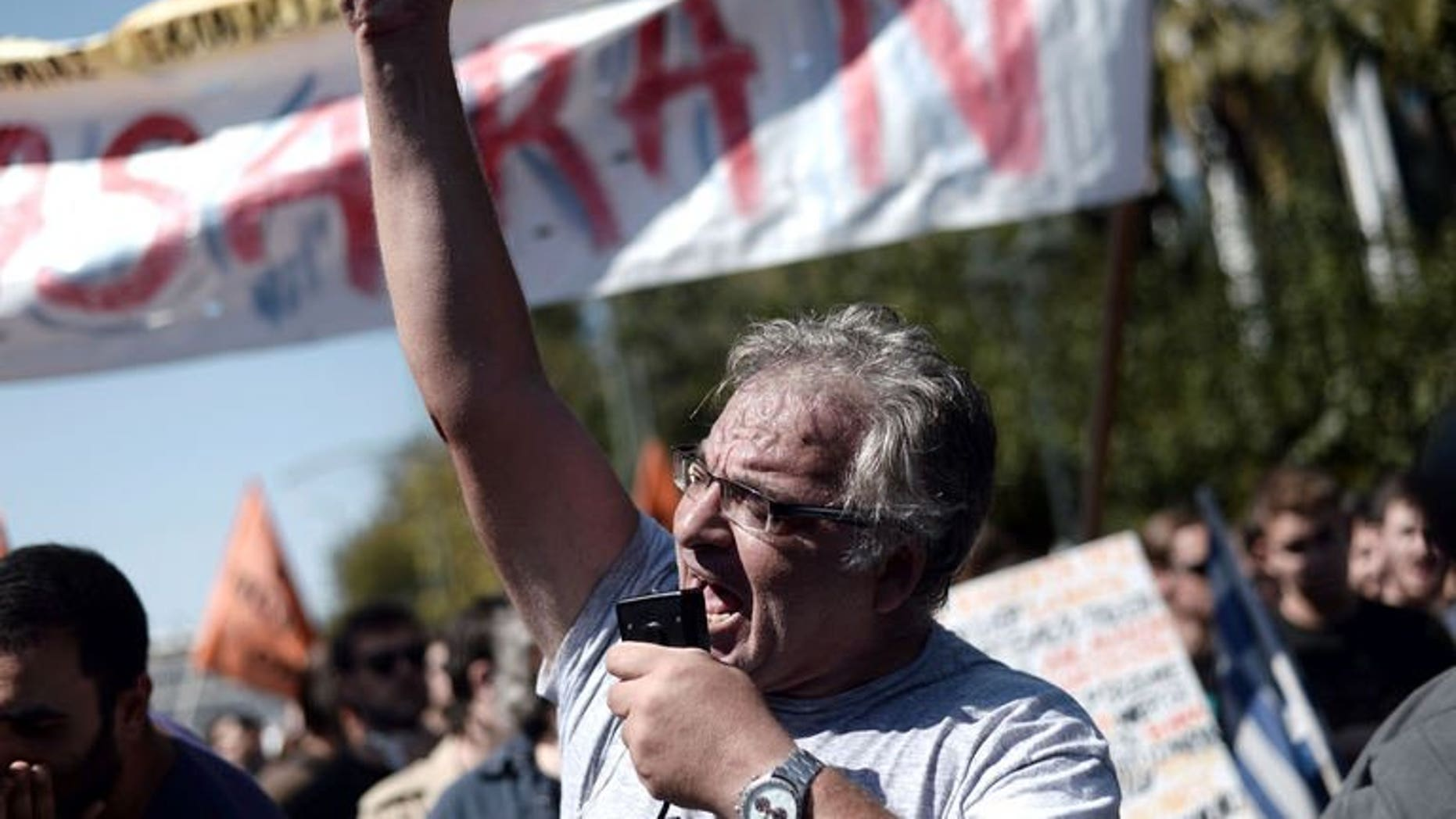 A Greek demonstrator shouts slogans during a rally in Athens, on September 24, 2013. Thousands of Greek civil servants have protested at the start of a fresh strike against job cuts pushed by the government in return for international bailout loans.