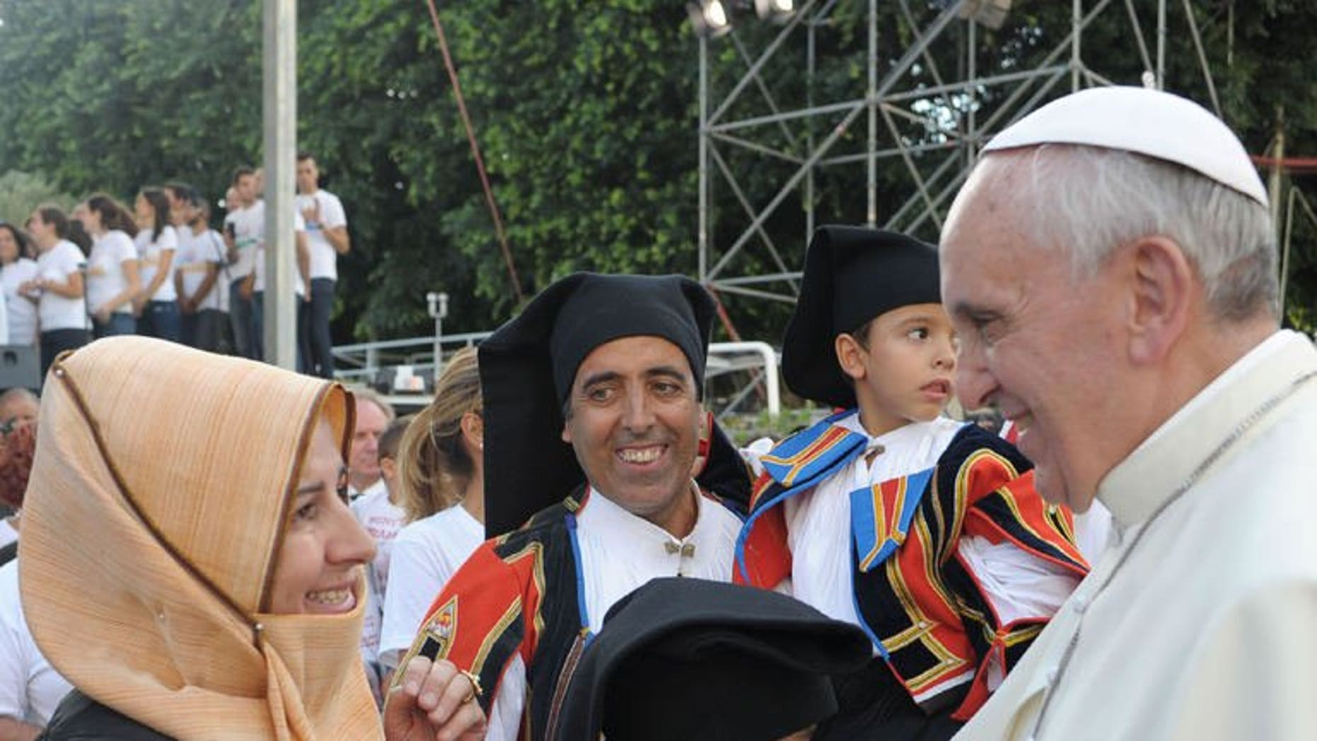 "Pope Francis meets worshippers during a visit to Cagliari, on September 22, 2013. Pope Francis has called on countries to protect migrants, condemning the treatment of refugees as mere ""pawns on the chessboard of humanity""."