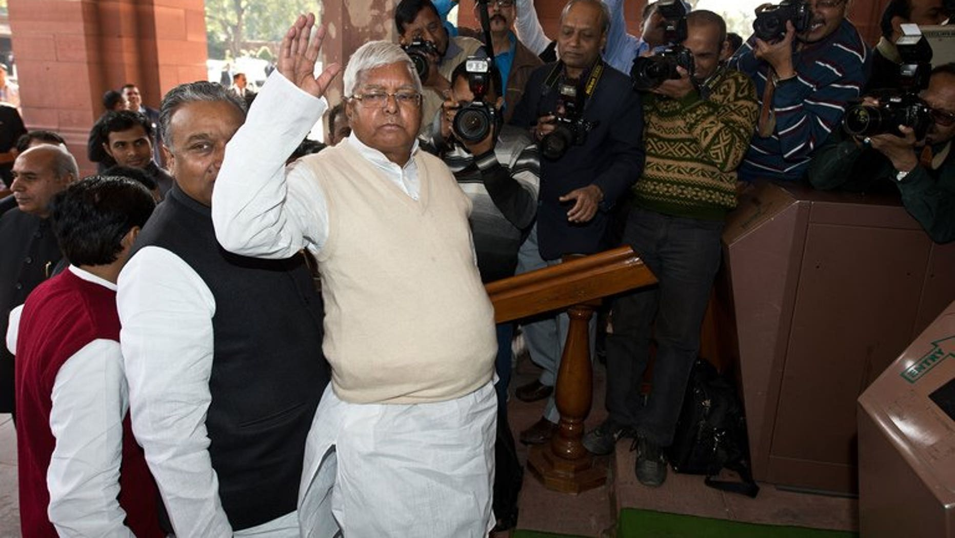 Former Railway Minister Lalu Prasad Yadav (C) arrives at Parliament for the unveiling of the Railway Budget in New Delhi on February 26, 2013.