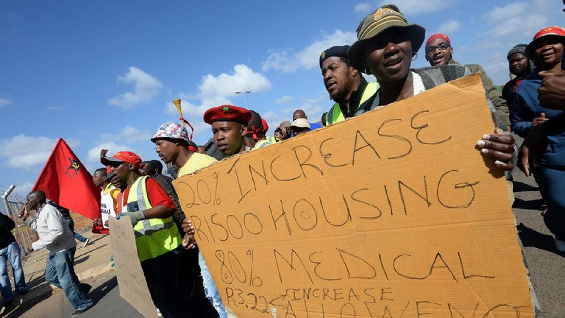 Workers on strike hold a placard asking for wage increases as they demonstrate outside Ford's plant in Pretoria on August 20, 2013.