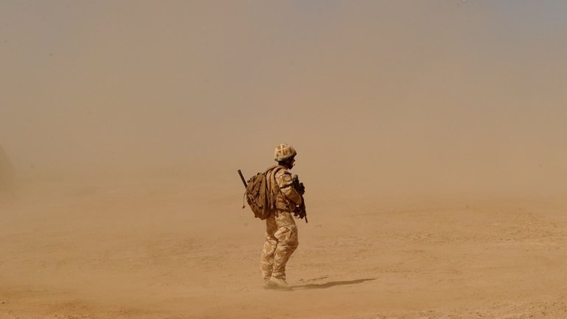 A British soldier walks near the Pimon military camp in Nad-e Ali district of Helmand province on March 25, 2010.