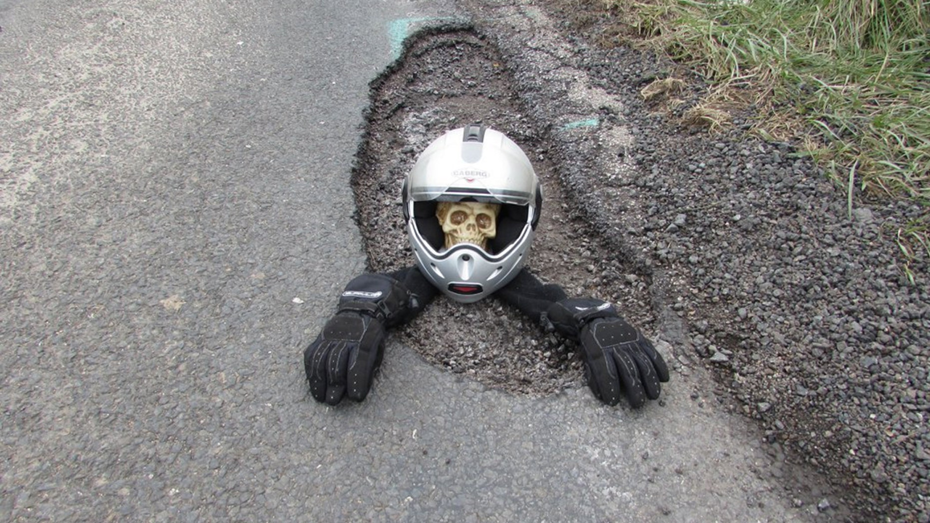 """A biker got so fed up waiting for the council to fill a huge pothole he staged these hilarious photos - of a SKELETON in a helmet peering out of it. See SWNS story SWPOTHOLE; Brian Joce, 64, says he was forced to take drastic action to highlight how big and dangerous the hole on the A3083 at the entrance to his village had become. Brian started to use his helmet and gloves to pretend the pothole was so deep a biker fell into it and took a few pictures. The day after, he decided to try and take pictures of the hole with a toy car and a rubber duck before returning 24 hours later with the skeleton. Brian explained that the pothole was first spotted ten or 15 days ago and that it was reported to Cornwall Council. He said that only after his pictures went viral the pothole was finally filled in. He added: """"It started on March 18, when we took a lot of pictures of the road. """"People on the Lizard Notice Board [Facebook page] were asking where it was or saying 'Oh, I just drove into it'. So I thought I'd just highlight it."""""""