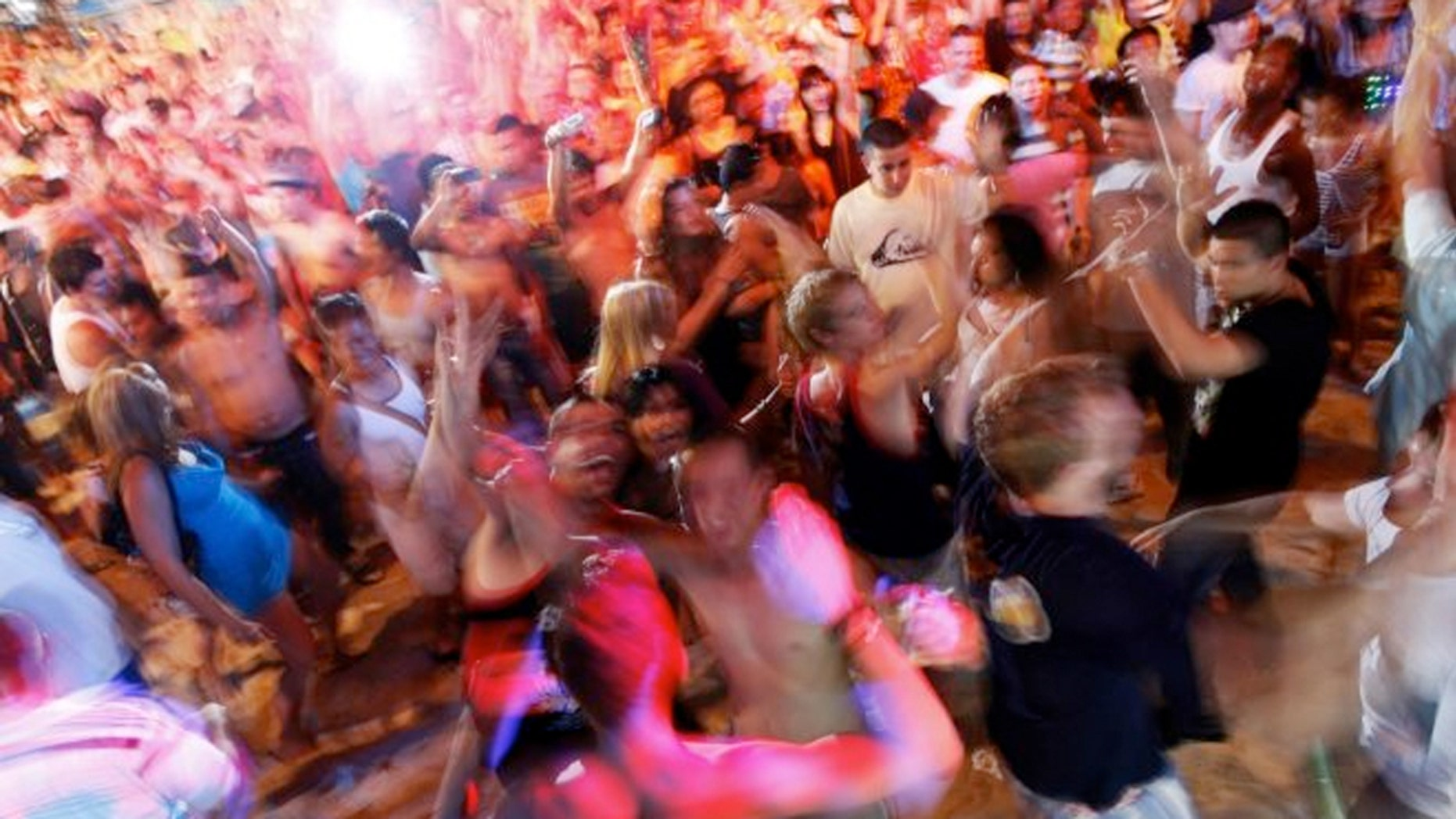 Tourists dance to electronic music during an open-air party at Patong beach in Phuket, one of Asia's premier resort islands. (Reuters)