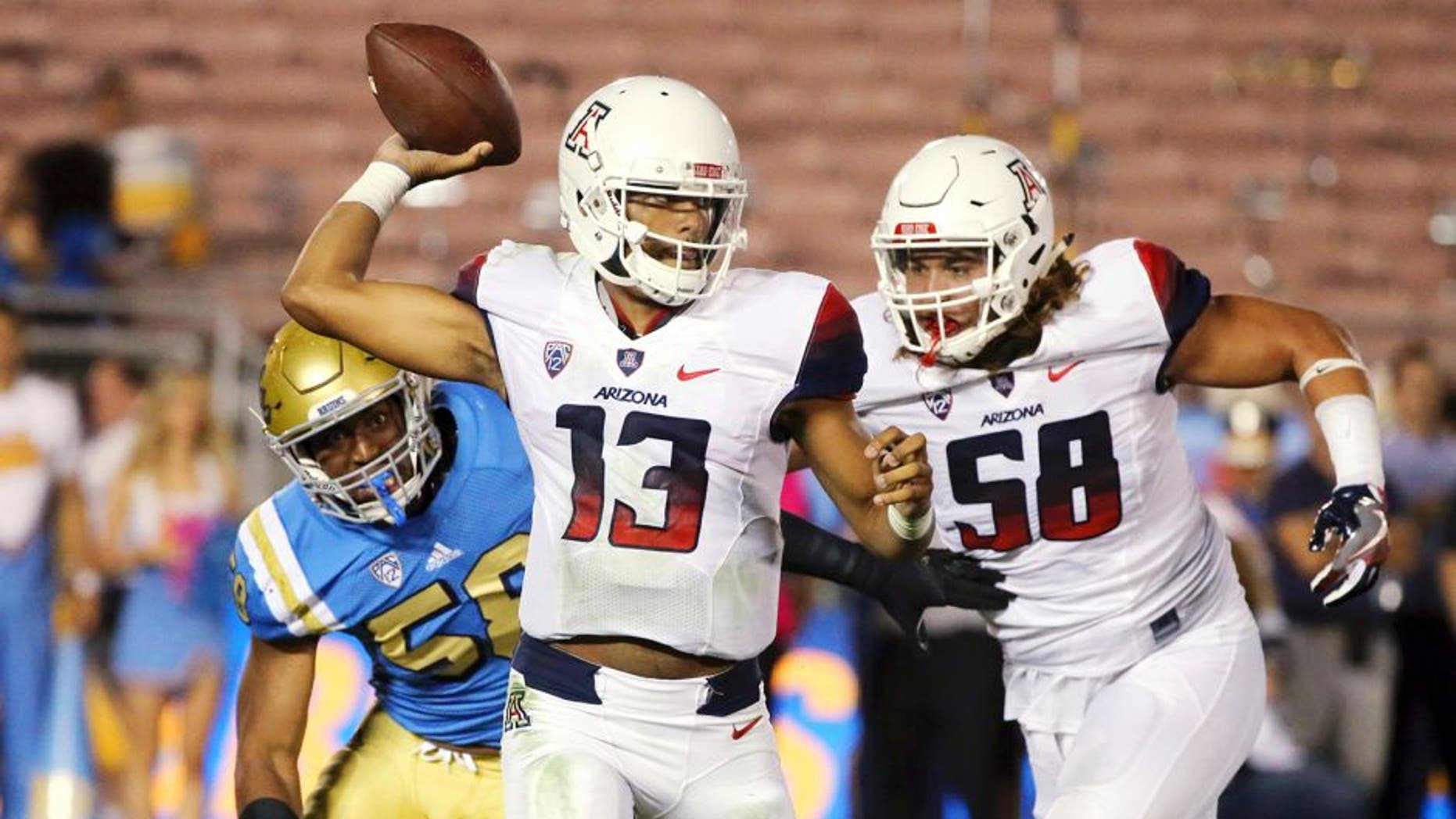 Arizona quarterback Brandon Dawkins (13) passes under pressure from UCLA defensive lineman Deon Hollins (58), left, with protection from Arizona offensive lineman Layth Friekh (58), right, in the first half of an NCAA college football game Saturday, Oct. 1, 2016, in Pasadena, Calif. UCLA won, 45-24. (AP Photo/Reed Saxon)