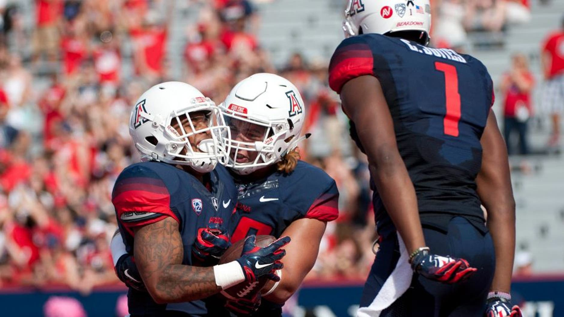 Oct 10, 2015; Tucson, AZ, USA; Arizona Wildcats running back Orlando Bradford (21) is congratulated by offensive lineman Layth Friekh (58) and wide receiver Cayleb Jones (1) after scoring a touchdown during the second quarter against the Oregon State Beavers at Arizona Stadium. Mandatory Credit: Casey Sapio-USA TODAY Sports