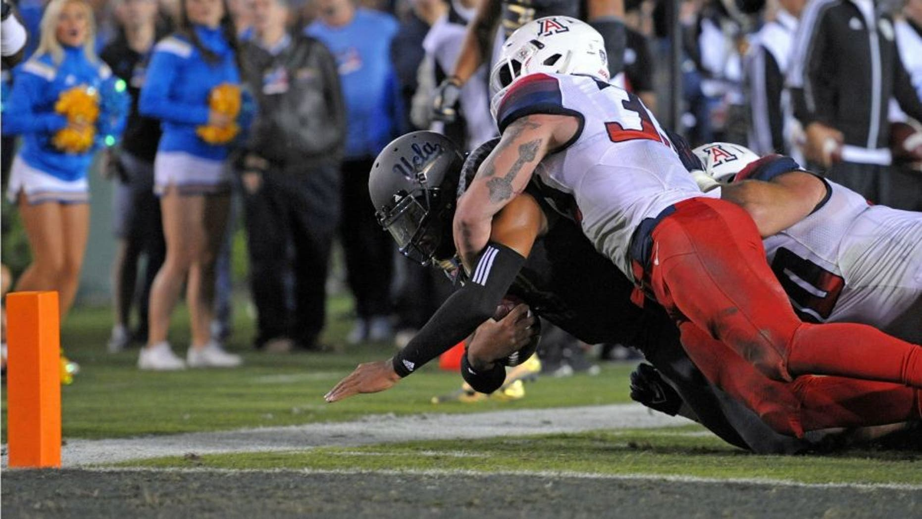 Nov 1, 2014; Pasadena, CA, USA; UCLA Bruins quarterback Brett Hundley (17) dives to the 2 yard line as Arizona Wildcats linebacker Scooby Wright III (33) brings him down during the second quarter at Rose Bowl. Mandatory Credit: Jake Roth-USA TODAY Sports