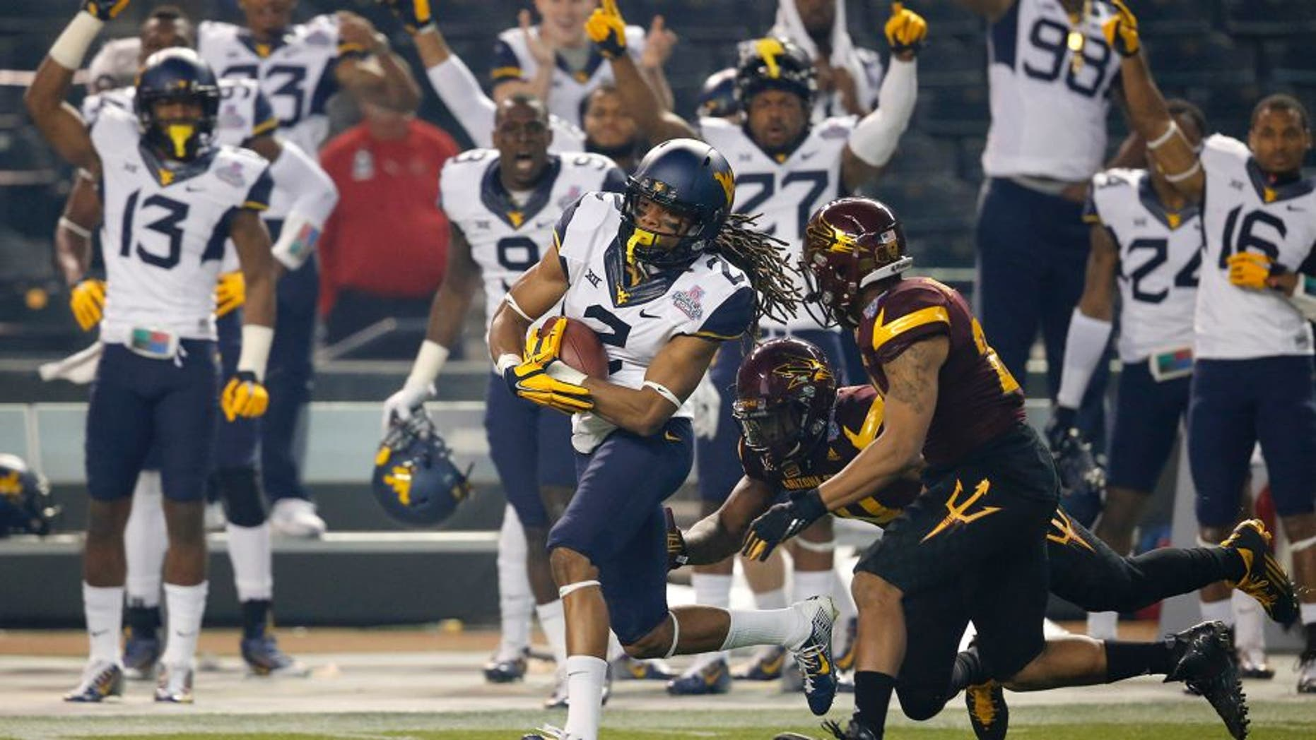West Virginia wide receiver Ka'Raun White (2) pulls in a pass as Arizona State defensive back Kweishi Brown (10) gives chase during the first half of the Cactus Bowl NCAA college football game, Saturday, Jan. 2, 2016, in Phoenix. (AP Photo/Ross D. Franklin)