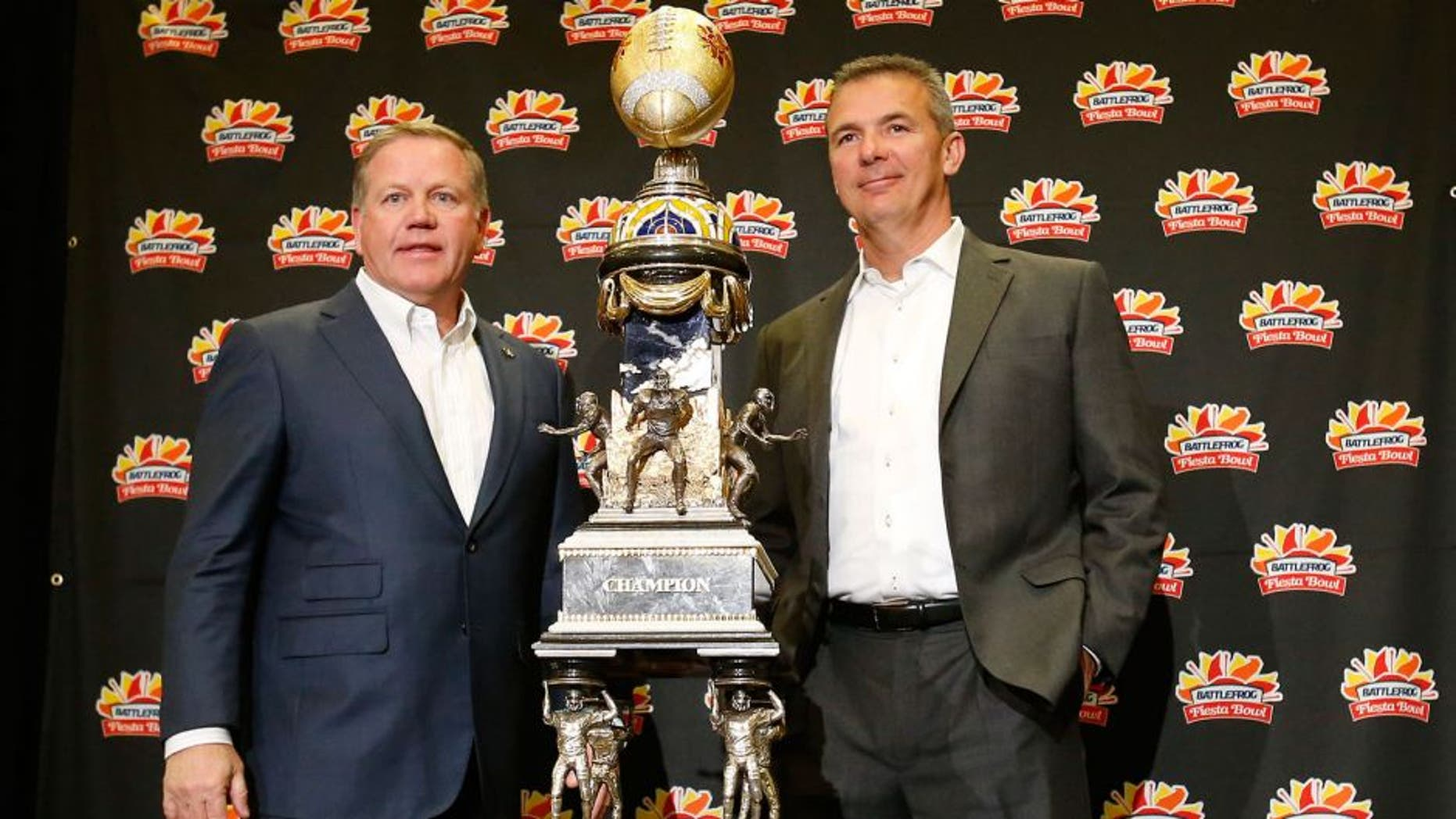 Notre Dame head coach Brian Kelly, left, and Ohio State head coach Urban Meyer pose with the trophy during a news conference for the Fiesta Bowl NCAA college football game, Thursday, Dec. 31, 2015, in Scottsdale, Ariz. Notre Dame plays Ohio State on New Year's Day. (AP Photo/Rick Scuteri)