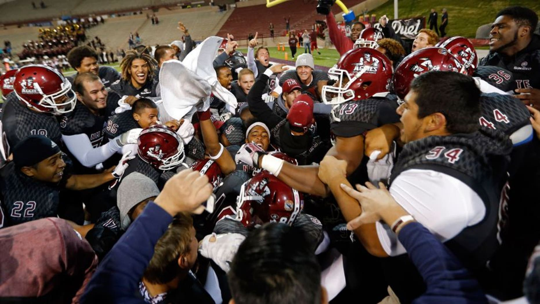 The New Mexico State team celebrate after defensive back Terrill Hanks intercepted a pass from Idaho quarterback Matt Linehan to win 55-48 in overtime their NCAA college football game in Las Cruces, N.M., Saturday, Oct. 31, 2015. (AP Photo/Andres Leighton)