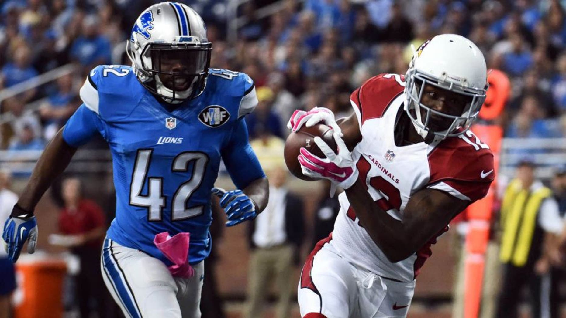 Oct 11, 2015; Detroit, MI, USA; Arizona Cardinals wide receiver John Brown (12) completes a pass for a touchdown during the second quarter while being pressured by Detroit Lions strong safety Isa Abdul-Quddus (42) at Ford Field. Mandatory Credit: Tim Fuller-USA TODAY Sports