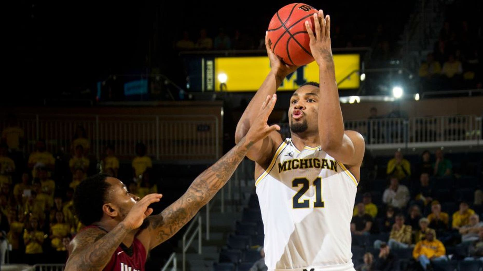 IUPUI guard Darell Combs, left, defends a jump shot from Michigan guard Zak Irvin (21) in the second half of an NCAA college basketball game at Crisler Center in Ann Arbor, Mich., Sunday, Nov. 13, 2016. Michigan won 77-65. (AP Photo/Tony Ding)