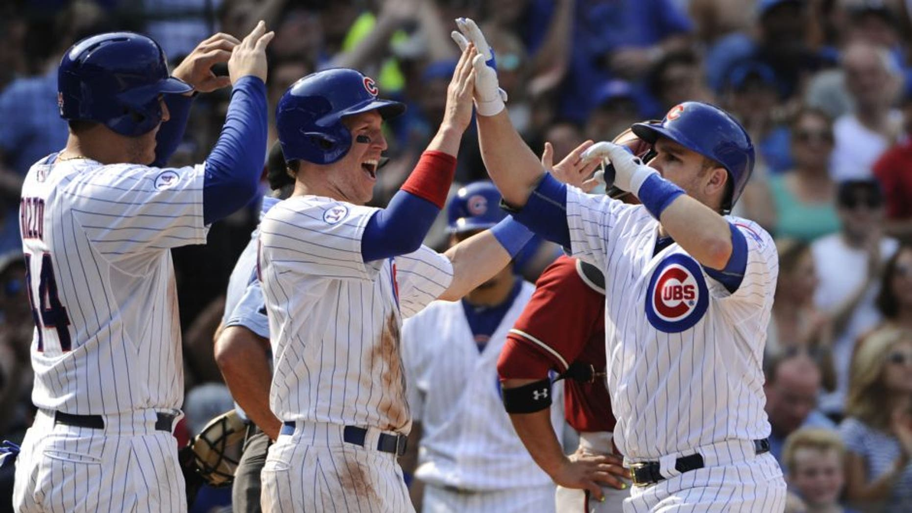 Chicago Cubs' Anthony Rizzo (44), left, and Chris Coghlan, center, high-five teammate Miguel Montero after he hit a grand slam off Arizona Diamondbacks' Matt Reynolds pitching in the sixth inning of a baseball game on Sunday, Sept. 6, 2015, in Chicago. (AP Photo/Matt Marton)