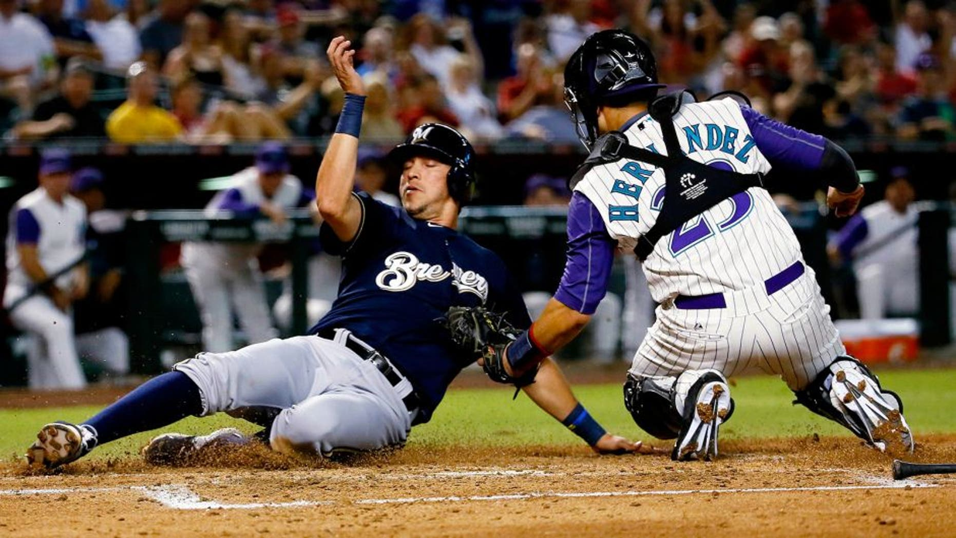 Milwaukee Brewers' Hernan Perez is tagged out at the plate by Arizona Diamondbacks' Oscar Hernandez while trying to score on a ground out by Gerardo Parra during the third inning of a baseball game, Thursday, July 23, 2015, in Phoenix. (AP Photo/Matt York)
